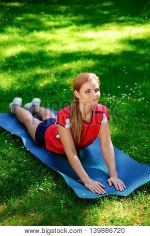 Yoga woman in a red t-shirt meditating in park