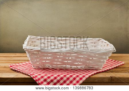 Empty white basket on checked red tablecloth