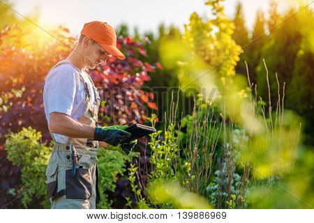 Garden Design with Tablet Device. Professional Gardener with His Tablet Computer.