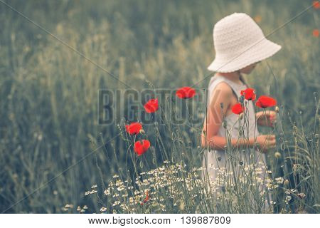 Joyful Childhood Scene. Joyful Child Between Poppy Flowers. Caucasian Girl on the Meadow.