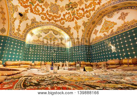 ISFAHAN, IRAN - OCT 15, 2014: Oriental restaurant in luxury style with dinning set glasses and persian carpet on floor on October 15, 2014. Third largest city in Iran Isfahan is example of Islamic culture