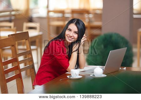 Young businesswoman using laptop in coffee shop. Successful businesswoman. Young woman with laptop sitting in cafe looking at the camera.