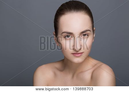 Beauty fashion vogue style face of caucasian brunette with elegant make-up blue eyes natural lips touching perfect skin. Close-up studio portrait isolated. Black background with grey spot. Toned.
