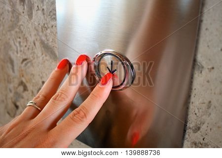 Female hand pressing elevator button for down.