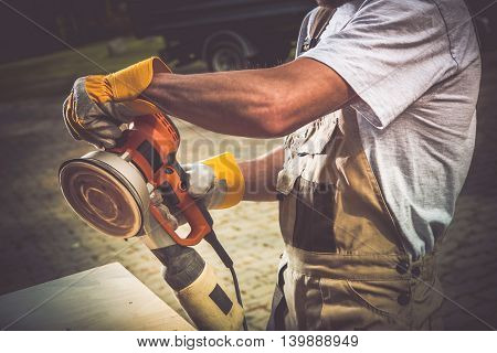 Sanding Machine In Action. Wood Sanding Closeup Photo. Men with Sanding Tool.