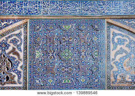 Old tiled design with traditional Persian patterns on wall of historical mosque