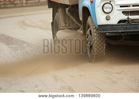 Road brush sweeper machine cleans dirt road and splashing mud