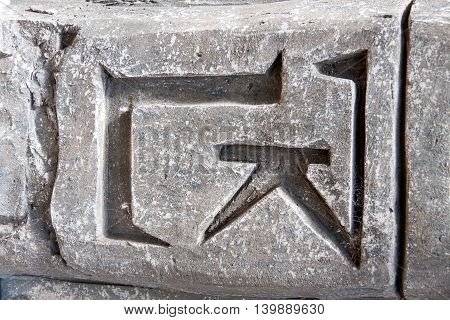decorative gray stone wall with symbols and hieroglyphs close-up.