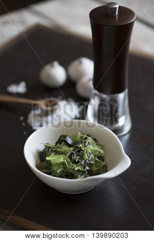 Salad from sea Kale, salt, garlic, pepper on a dark Board