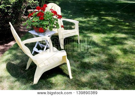 2 chairs with flowers between them on a lawn