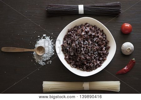 Black rice, rice noodles, salt, garlic, tomato, pepper on a dark Board, top view