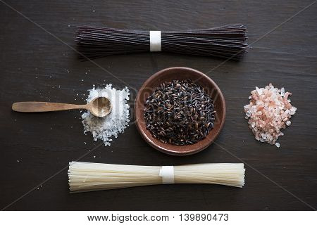 Black rice, rice noodles, pink salt on a dark Board, top view