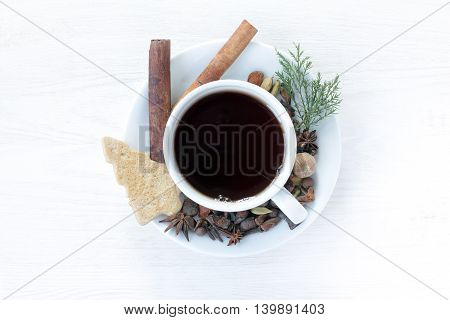 Black tea in a white mug placed on a table decorated with spices and a top view / Festive table setting of tea