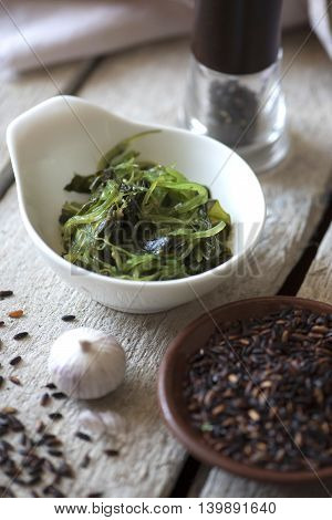 The seaweed salad, black rice, garlic, pepper on wooden background