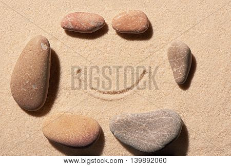Small And Large Sea Stones With Smile Drawn On Sand