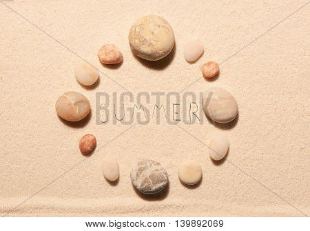 Round Frame Of Sea Stones With Summer Lettering Drawn On Sand