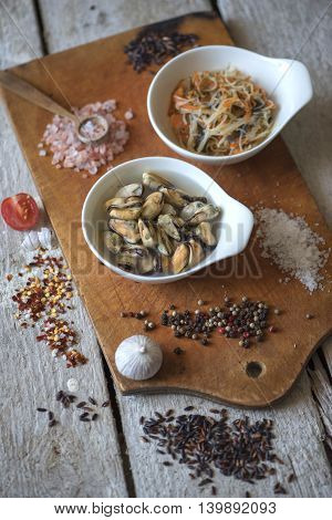 Funchoza salad and mussels on wooden background