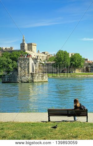Girl sitting in front of the Famousmedievalbridgein the town ofAvignon, in southernFrance