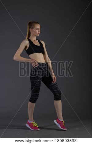 slim female in activewear doing posin on gray low key perfect sport woman