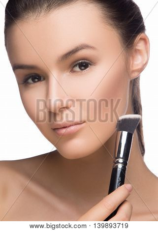Closeup portrait of a woman applying dry cosmetic tonal foundation on face using makeup brush.