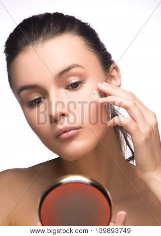 Portrait of young woman applying moisturizer cream on her pretty face white background
