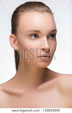 Glamour portrait of beautiful woman model with fresh daily makeup and romantic wavy hairstyle. Fashion shiny highlighter on skin sexy gloss lips make-up and eyebrows