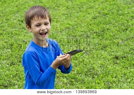 Happy child with mobile phone outdoor in nature. Childhood, technology, leisure concept