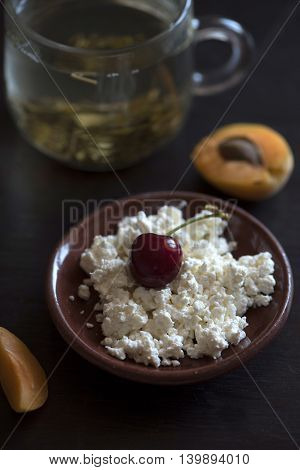 Green tea in transparent Cup, cottage cheese, peach and cherry