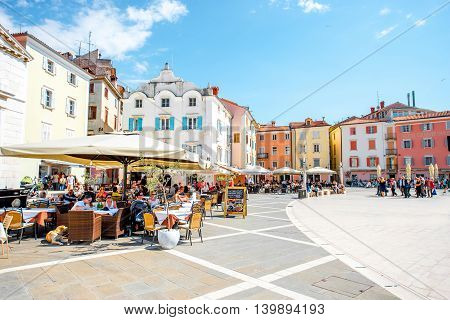 Piran, Slovenia - May 7, 2016: Tartini main square with people eat at the cafe and restaurants in Piran town. Piran is one of Slovenia's major tourist attractions.
