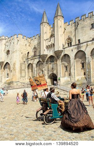 AVIGNON, FRANCE - JULY 19, 2014: Actors in historical costumes advertising their performance in front of the Papal Palace during famous theatre festival from July 4 to 27 2014 in Avignon south of France.