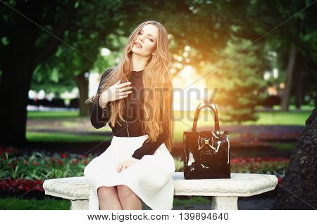 Woman seating on the bench enjoying nature in sunny day outdoors charming young girl relaxing in the summer park female student relaxing at campus flare sun light