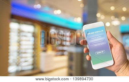 Woman hand holding smartphone against blur bokeh of airport background check-in online concept