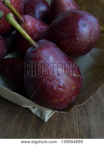 Red ripe pears in a paper bag on a wooden table