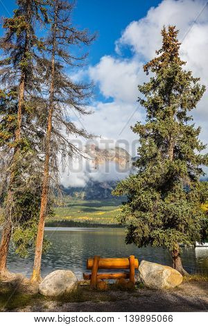 Early morning on cold Pyramid Lake, Jasper National Park. On the shore - a cozy wooden bench for relaxing