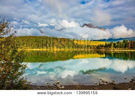 Warm autumn day in park Jasper, the Rocky Mountains of Canada. Charming Patricia lake among evergreen forests, yellow bushes and far mountains
