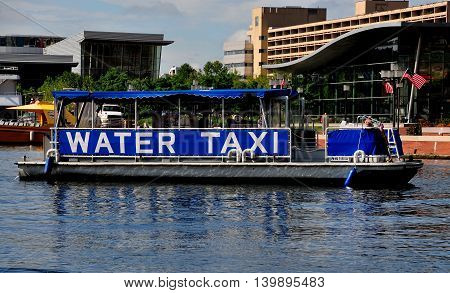 Baltimore Maryland - July 22 2013: A city water taxi pulls into the Inner Harbor dock