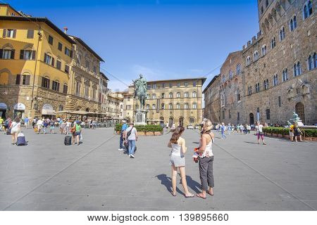 Florence, Italy, June, 25, 2016: tourists on a square infront of Palazzo Vecchio - one of the famoust buildings in Florence, Italy
