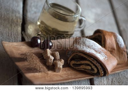Sweet rolls baked on a wooden stand, lump sugar, cherries and green tea in a transparent Cup