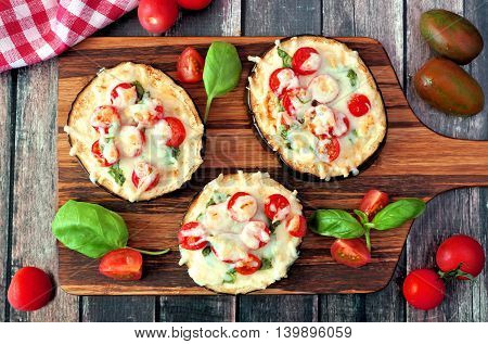 Healthy Eggplant Mini Pizzas With Melted Mozzarella, Tomatoes And Basil On A Serving Board Against R