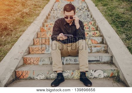 A guy in a nice town, walking, listening to music and taking pictures themselves on the phone
