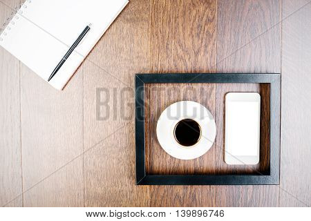 Top view of dark wooden table with spiral notepad pen coffee cup and blank white smartphone inside picture frame. Mock up