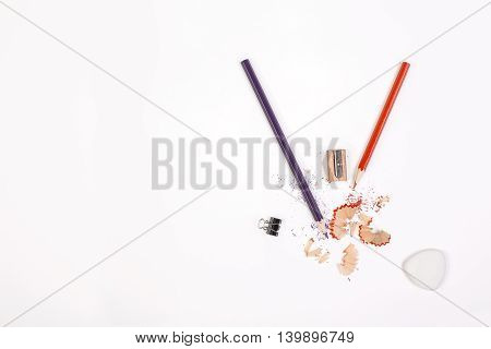 Top view of white desktop with pencils sharpener sawdust small peg and eraser