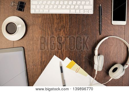 Top view of messy workplace with tablet headphones smartphone computer keyboard coffee cup stationery and other items. Mock up