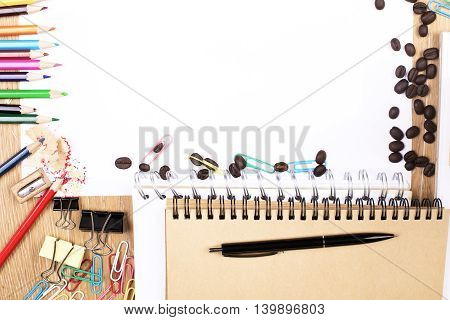 Wooden desktop with blank paper sheet and colorful supplies. Mock up