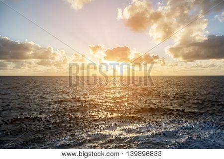Sunset in the open ocean under cloudy sky.
