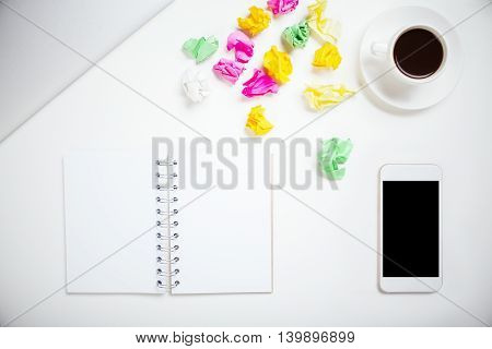 Top view of messy white office desktop with crumpled paper blank spiral notepad smart phone coffee cup and closed laptop. Mock up