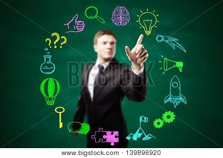 Blurry businessman pointing at circular business icons sketch on blackboard background. Success and idea concept