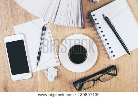Light wooden table with blank smartphone coffee cup glasses book crumpled paper balls notepad and pens. Mock up