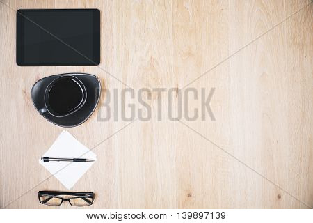 Light wooden desktop with blank tablet coffee cup pen paper sheets and glasses on its left side. Mock up
