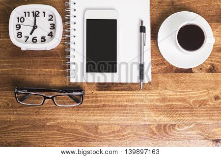 Top view of wooden desktop with clock glasses blank smartphone spiral notepad pen and coffee cup on saucer. Mock up